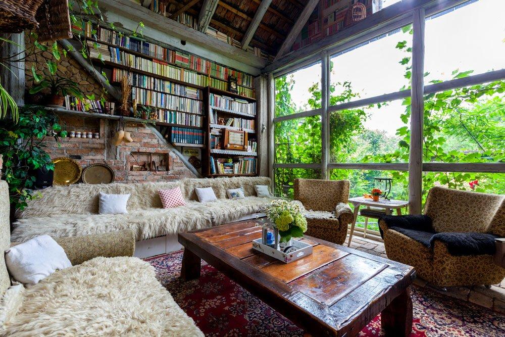obývací pokoj ve zrekonstruované stodole s masívním dřevěným stolem, gaučem s kožušinami, retro křeslami, barevným tkaným kobercem, velikou knihovnou a prosklenou stěnou s výhledem na stromy