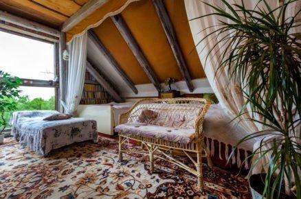 ložnice ve stodole s postelí, pleteným sezením a květinovým kobercem