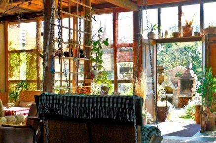 stodola zrekonstruovaná na bydlení s prosklenou zdí a hojdačkou vyrobenou ze starého křesla
