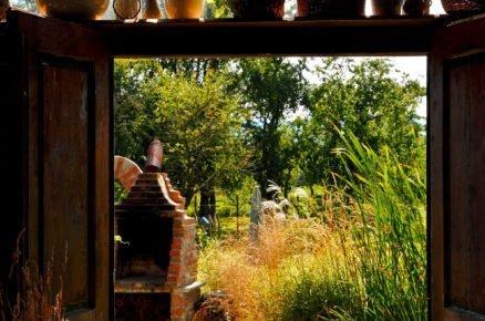 výhled ze stodoly do zahrady s murovaným krbem