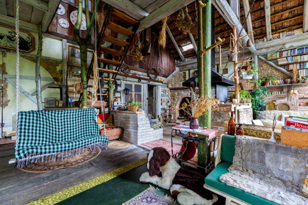 interiér zrekonstruované stodoly pro bydlení se sezením, krbem a různymi zběratelskými předměty