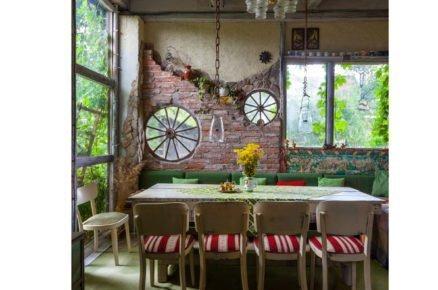 jídelna v obydlené stodole s pohovkou a dřevěnými židlemi, cihlovou zdí a kolesy od vozů místo oken