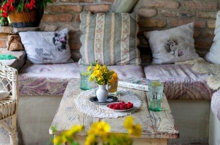 sezení na terase u zrekonstruované stodoly s dřevěným stolem, pohovkou a cihlovou zdí, která odděluje terasu od zahrady