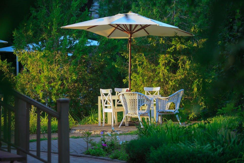 zahradní sezení se slunečníkem v podvečer