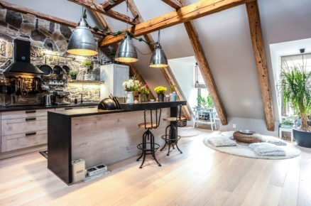 kuchyň s barovým ostrůvkem, stěna je obložená kamenem, který ladí s původními trámy