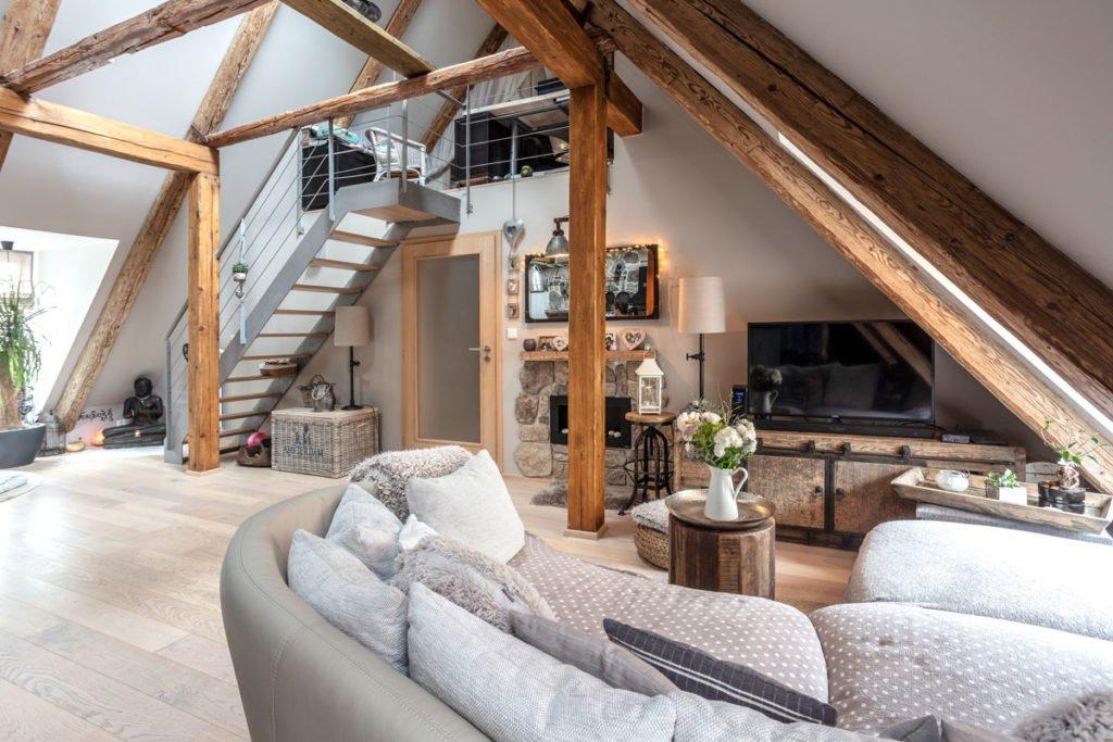Obývací pokoj ve venkovském stylu. Do patra vede kovové schodiště, pokoj je zařízený masivním dřevěným nábytkem, součástí pokoje jsou dřevěné trámy
