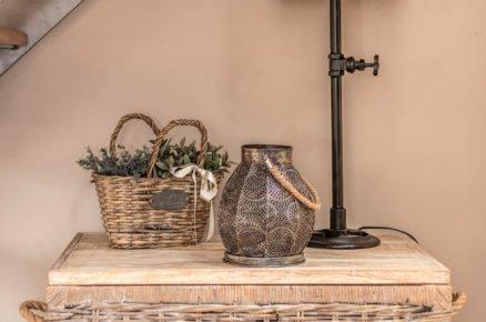 proutěný koš s industriální lampou, svícnem a pleteným košíčkem