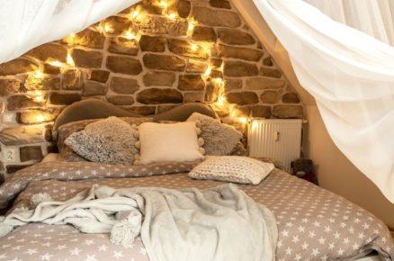 romantická venkovská ložnice se stěnou z kamene a nebesama