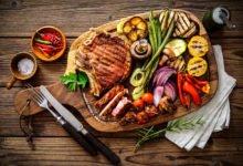 dřevěné prkno s grilovaným steakem a s mixem grilované zeleniny