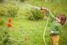 malé dítě zalévá zahradu rozstřikovací hlavicí