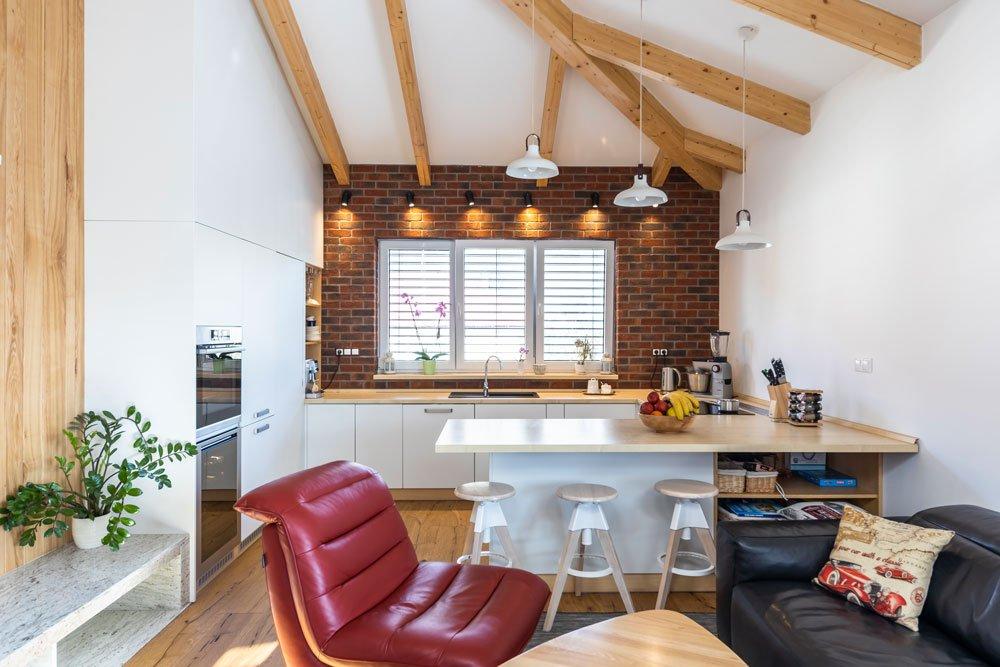 obývací pokoj s kuchyní s dřevěným nábytkem, koženými sedačkami, cihlovým obkladem a přiznanými trámy