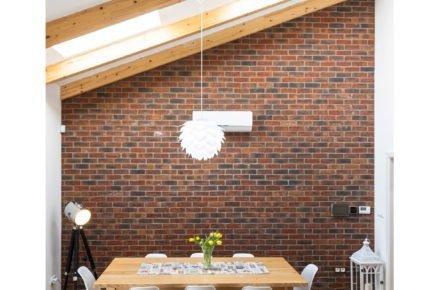 jedálenský dřevěný stůl v interiéru s cihlovou stěnou