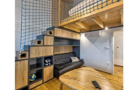 industriální interiér s dřevěným nábytkem a síti místo zábradlí