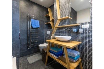 koupelna s umyvadlem na desce a s atypickými dřevěnými policemi na kostkovaném tmavém obkladu