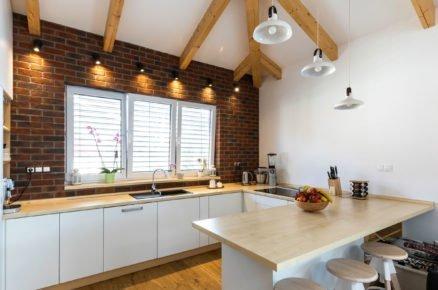 kuchyň s jídelným pultem zařízená dřevěným nábytkem