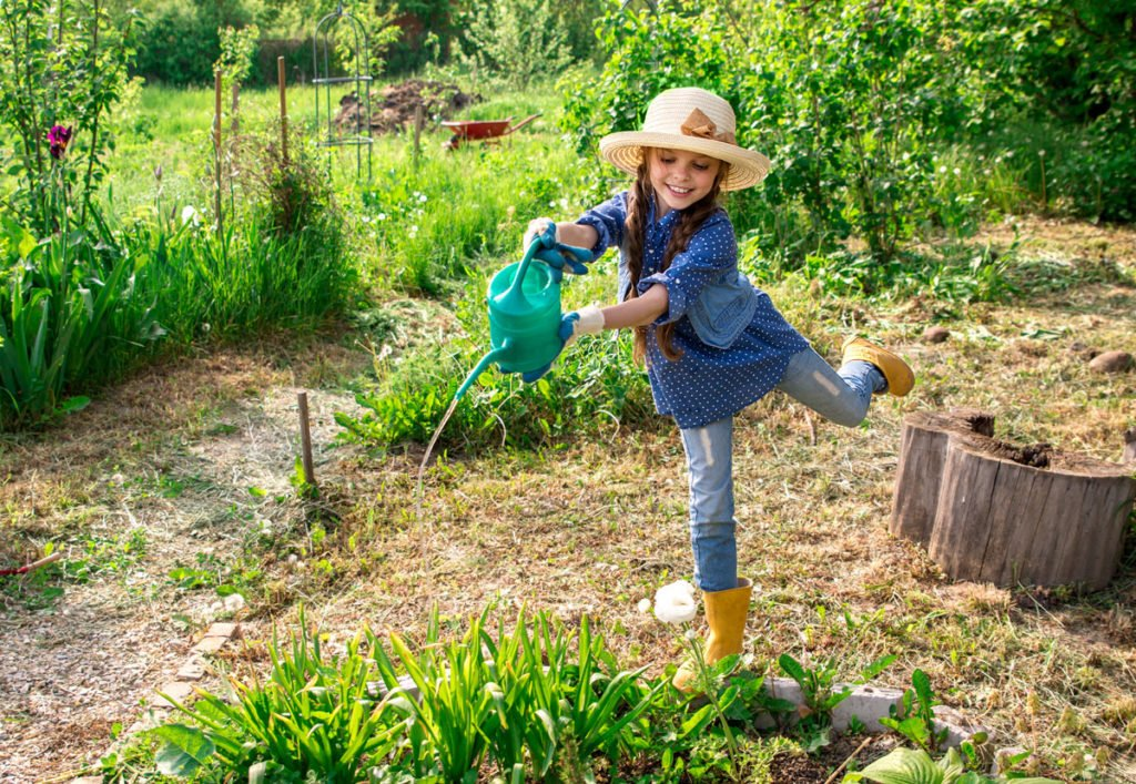 dívka zalévá květiny na zahradě