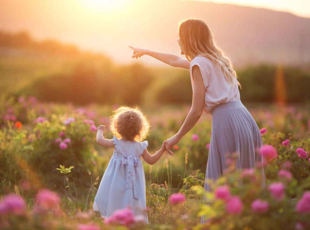 matka s dítětem v zahradě během západu slunce