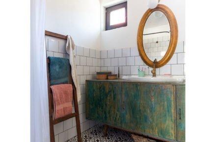 koupelna se zelenou lazúrovanou skříňkou, mosazným zrcadlem a vzorovanou podlahou