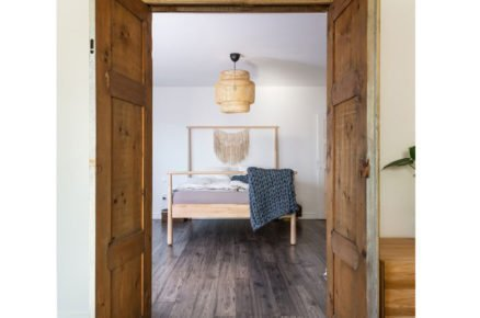 pohled do ložnice v natur stylu s vlněným přehozem cez postel