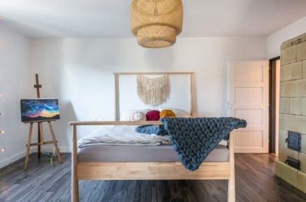ložnice s dřevěnou postelí s vlněným pleteným přehozem