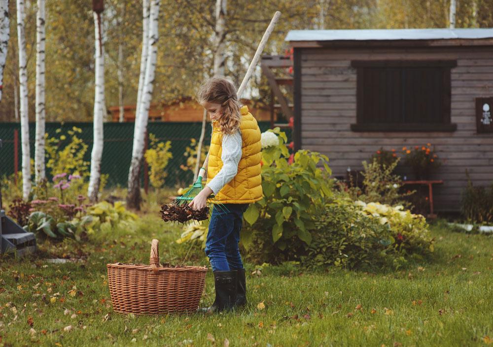 dívka sbírá lístí v listopadové zahradě