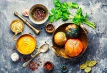stůl s nádobama s hokkaido dýni, kořením, hokkaido krémém a bylinkama