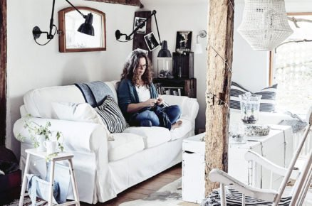 interiér v rustikálním stylu, s bílou sedačkou, bílým houpacím dřevěným křeslem, dřevěnou bílou komodou a původním dřevěným trámem