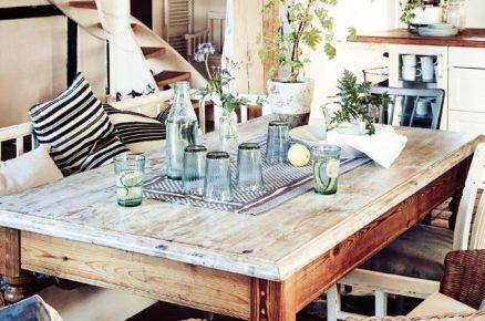 jídelna ve venkovském stylu, s dřevěným stolem, lavicí a proutěným křeslem, točitým schodištěm a dřevěnými trámy