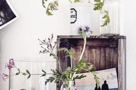 dekorace ze sklených váz a dřevěné bedýnky