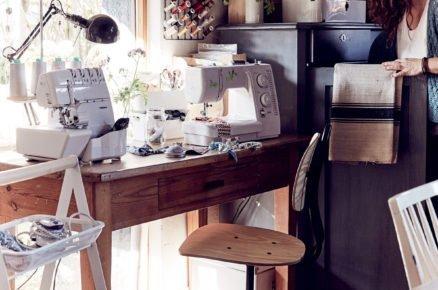 pracovní stůl ve venkovském stylu se šicím strojem, organizérem na kolečkách a otáčavou dřevěnou industriální židlí