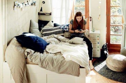 dětský pokoj s bílou postelí a povlečením v přírodních barvách, s policemi, nočním stolečkem a pleteným přírodným pufem