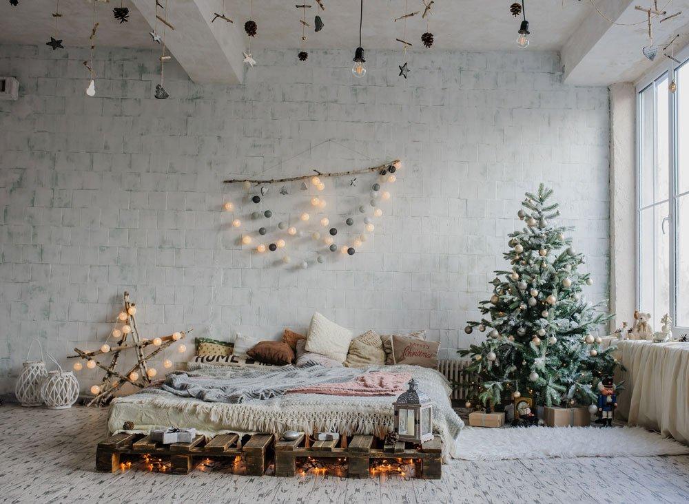 loftová ložnice ve skandinávskem stylu s vánočním stromem, světelnou girlandou a hvězdou vyrobenou z větev