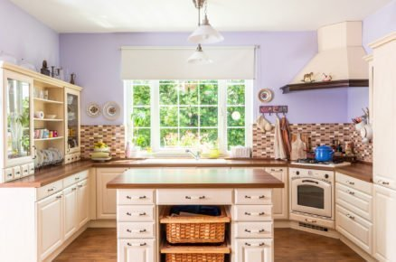 kuchyň ve venkovském stylu v bílé barvě s dřevěnou pracovní deskou a ostrůvkem