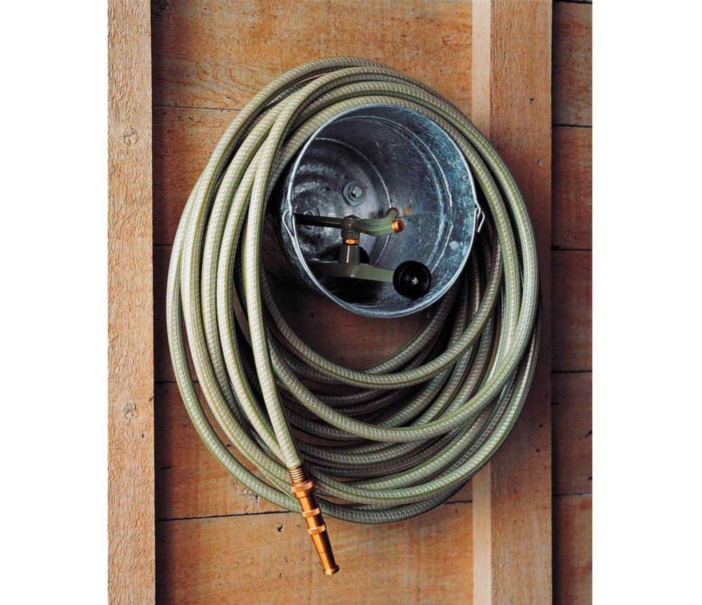 zahradní hadice zavěsená na děravém kbelíku