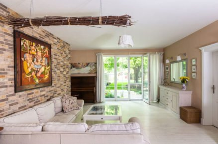 obývací pokoj se vstupem do zahrady ve venkovském stylu s bílou pohovkou, skleněným stolkem, bílou komodou, klavírem a cihlovou zdí