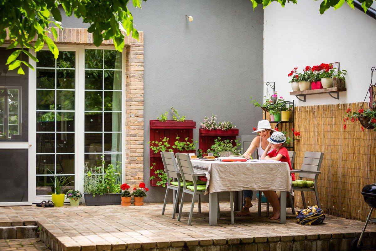 matka s dítětem dělají domácí úkoly na dřevěné terase rodinného domu