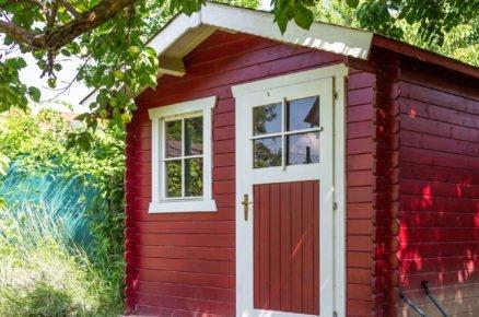 zahradní domek v rudé barvě pod stromem