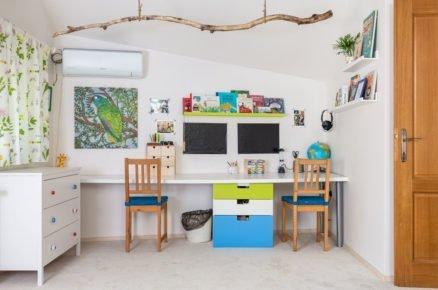 dětský pokoj s nábytkem v bílé, modré a zelené barvě, s komodou, pracovním stolem, stoličkama, barevnými závěsi a větvou zavěsenou ze stropu
