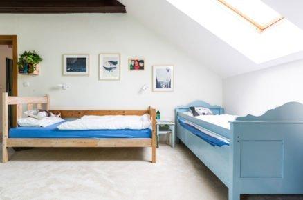 dětský pokoj v podkroví ve venkovském stylu s modrou dřevěnou postelí a postelí v přírodné barvě dřeva