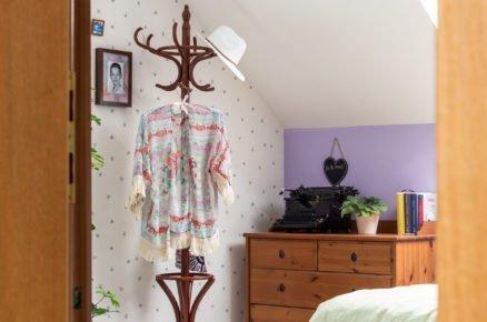 ložnice v podkroví rodinného domu ve venkovském stylu s komodou, bílou postelí a věšákem na oblečení