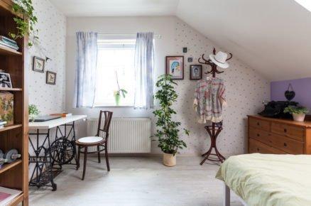 ložnice v podkroví ve venkovském stylu s dřevěnou komodou, postelí, věšákem na oblečení, stolkem vyrobeným ze starého šicího stroje a vzorovanou tapetou na zdech