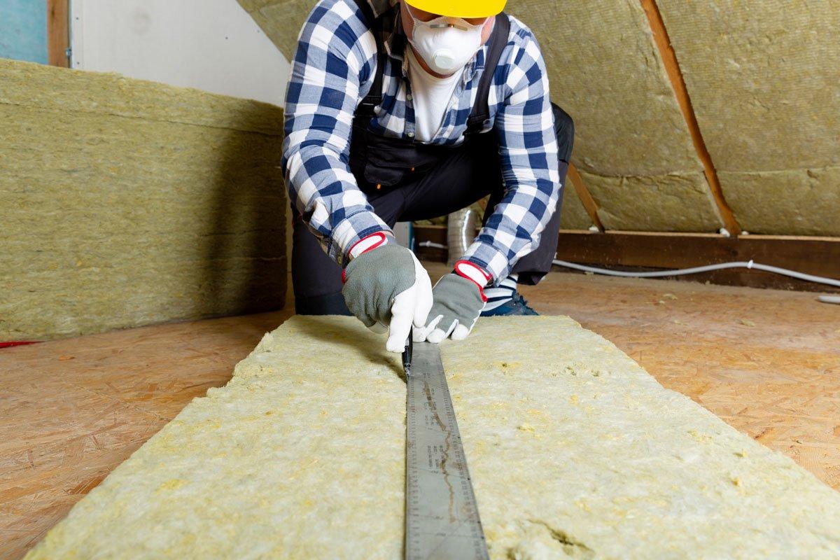 Řezání minerální vlny při zateplování šikmé střechy.