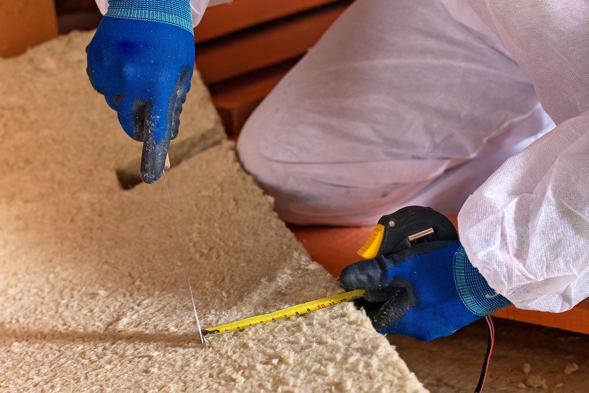 Vyřezávání minerální vlny při zateplování šikmé střechy.