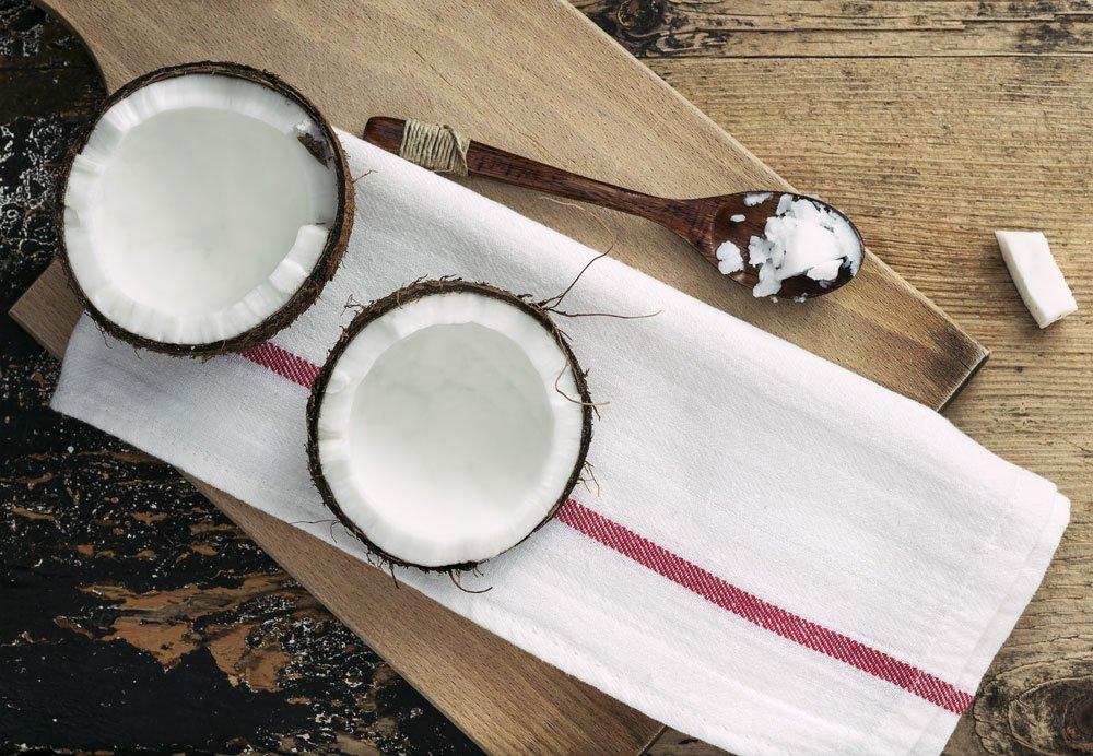Využití kokosového oleje v domácnosti: kokosový ořech a vařecha s kokosovým olejem