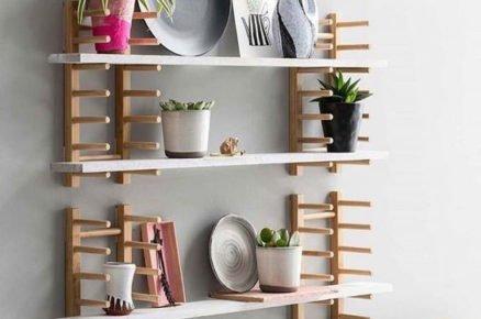 Dřevěný stojan na knihy nebo nádobí jako součást policového dílu na stěnu.
