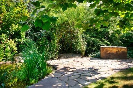 zahrada s altánkem z vrbového proutí a dřevěným hranolem na posezení