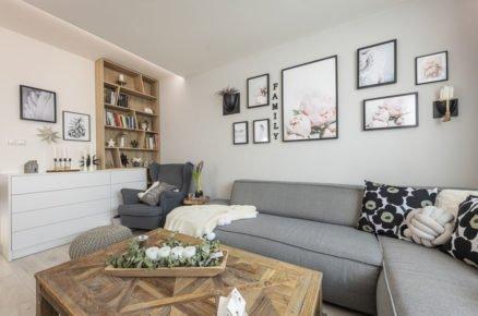 Obývací pokoj v severském stylu, s šedou pohovkou, dřevěným stolem a knihovnou a obrazy