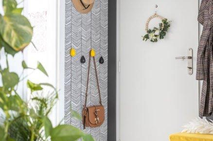 Chodba se vzorovanou tapetou na stěně a barevnými úchyty na pověšení oblečení