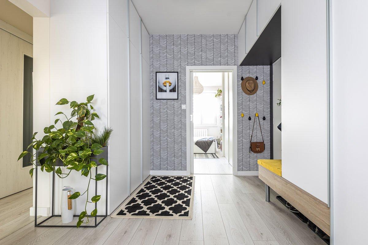 Interiér vstupní chodby se vzorovanou stěnou a vstavanou skříni v bílé a šedé barvě se žlutým akcentem.