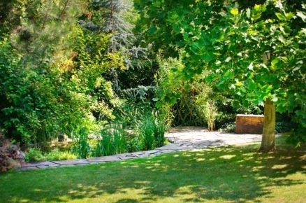 Pohled do zahradní části s chodníkem z kamene, jezírkem a altánkem z vrby.